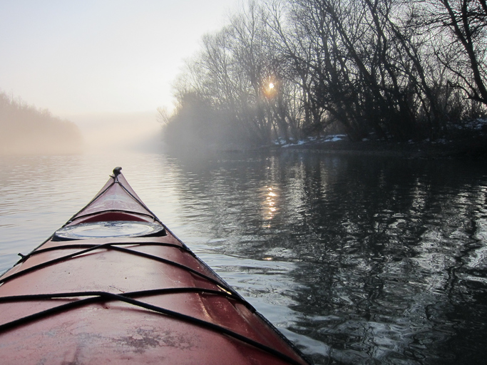 Red kayak in the foggy river. Winter kayaking in Danube river